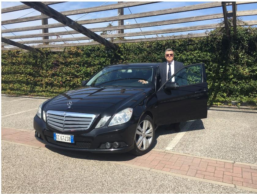 Ronberto Menegatti, tiotlare di AutoElite, accanto alla sua vettura da noleggio NCC con autista